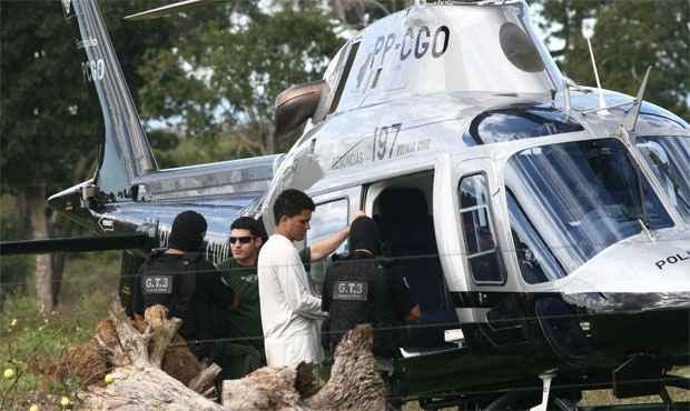 O acusado Aparecido Alves, de 22 anos, acompanhado de policiais, embarca em um helicoptero momentos antes de sua queda, em Goias (BENEDITO BRAGA/JORNAL HOJE/AE GO )